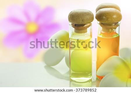 bottles with natural aroma oil over nature background. - stock photo