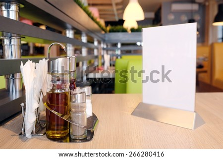 Bottles with olive oil, vinegar, salt and pepper, napkin on the table in restaurant - stock photo