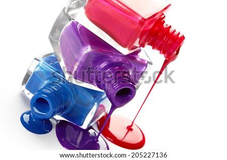 Bottles with spilled nail polish isolated on white background - stock photo