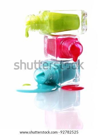 Bottles with spilled nail polish over white background - stock photo