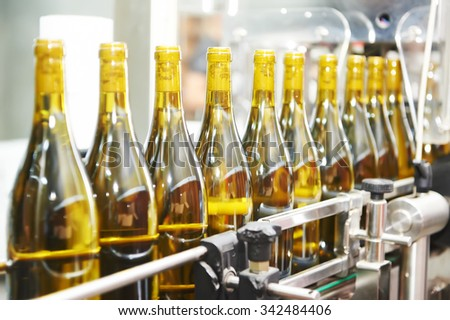 bottles with wine on bottling and sealing conveyer production  line at modern winery factory. Shallow DOF. - stock photo