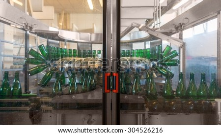 Bottling machine with many bottles in the factory - stock photo