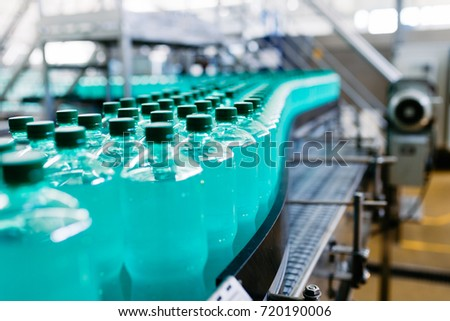 Bottling plant - Water bottling line for processing and bottling carbonated water into green bottles. Selective focus.