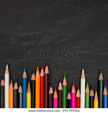 Bottom border of colorful pencil crayons against a blackboard background - stock photo