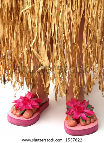 bottom half of a girl wearing a grass hula skirt and pink flowered flip flop sandals - stock photo