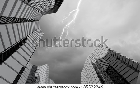 Bottom image of skyscraper with thunder lightning in sky - stock photo