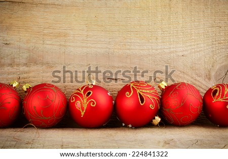 Bottom line of red baubles christmas ornaments on wooden surface planks - stock photo