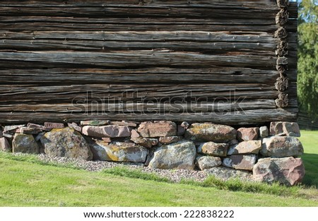 Bottom of a log hut built on a slope in Sweden. - stock photo