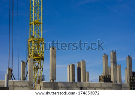 Bottom of tower crane on construction site between concrete piles. - stock photo