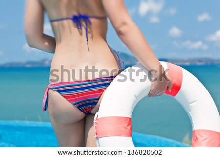 bottom of Young woman with floating equipment enjoying the ocean view - stock photo