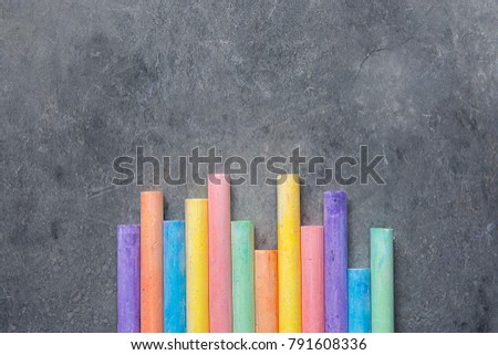 Bottom Rows of Multicolored Chalks on Dark Stone Blackboard Background. Business Creativity Graphic Design Crafts Kids School Concept. Copy Space