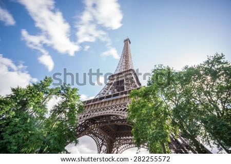 Bottom-up view of Eiffel tower dream with clouds, long exposure - stock photo