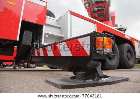 Bottom view of at the pull-out support of big red fire engine at day - stock photo
