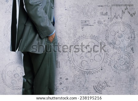 Bottom view of businessman and sketches of ideas on wall - stock photo