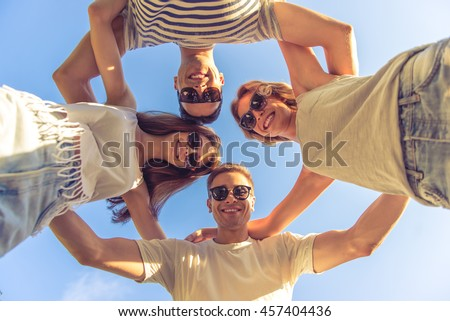 Bottom view of young beautiful people in casual clothes and sun glasses hugging, looking at camera and smiling while resting outdoors. Sky in the background - stock photo