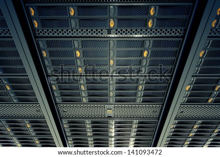 Bottom view on data servers while working. Blue LED lights are flashing. Image can represent cloud computing, information storage, etc. or can be the perfect technology background. - stock photo