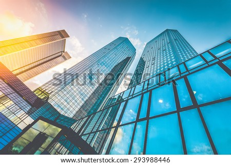 Bottom wide angle view of modern skyscrapers in business district in beautiful evening light at sunset with monochrome retro vintage Instagram style filter and lens flare effect - stock photo