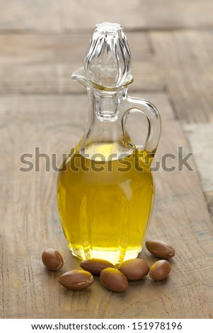 Botttle of Moroccan Argan oil and nuts  - stock photo