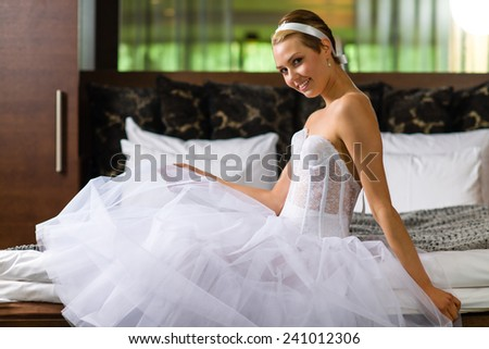 Boudoir, attractive young woman wearing lingerie and underskirt and she sits on the bed - stock photo