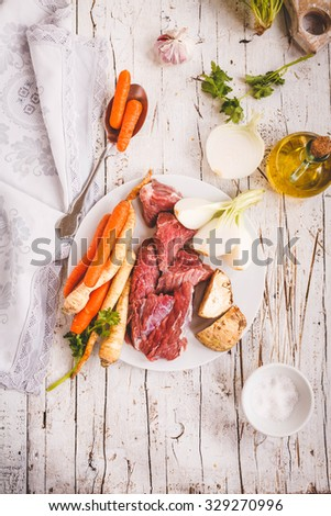 Bouillon ingredients concept. Include beef meat butcher, fresh roots and herbs on a white wooden vintage table with bottle of olive oil.. Rustic neutral style. natural day light. - stock photo
