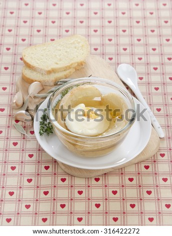 bouillon with poached egg garlic herbs in a transparent piala on a white plate with white bread in the background