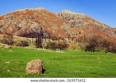 Boulder before the hills. A lone boulder stands in front of the impressive hills along the side of the Greater Langdale Valley. - stock photo
