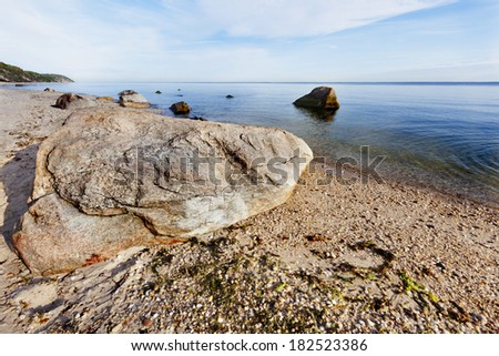Boulder lying by the seashore of the Peconic bay. Long Island, New York. - stock photo
