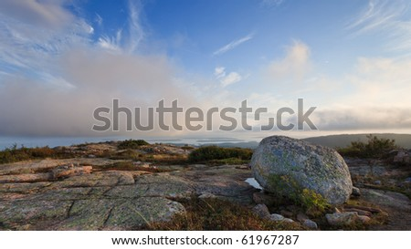 boulder on top cadillac mountains, around sunset with view of the atlantic ocean - stock photo