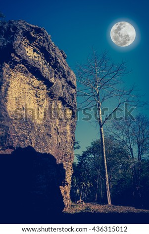 Boulders against beautiful sky and full moon over tranquil nature. Idyllic rural view of pretty surroundings. The moon taken with my own camera, no NASA images used. Cross process and vintage tone. - stock photo