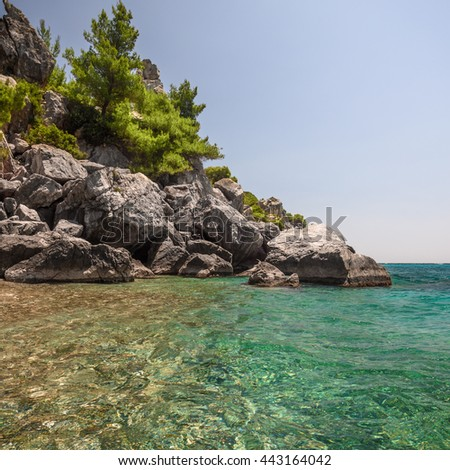 Boulders and fir trees on the rock in the hidden bay - stock photo