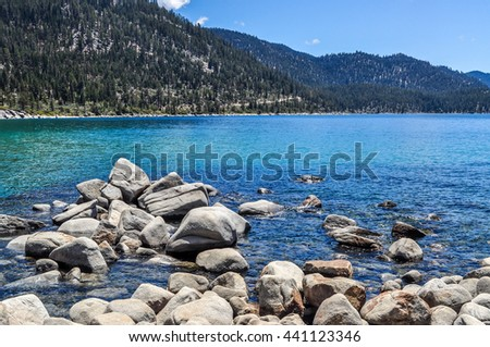 Boulders and large rocks line part of the shoreline of Lake Tahoe.