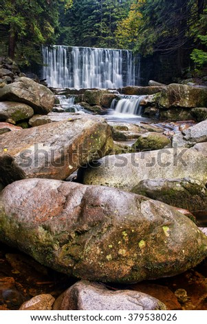 Boulders by the waterfall in mountain forest - stock photo