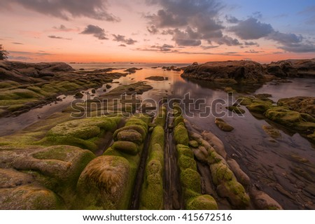 boulders of rocks sunset seascape. Image may contain soft focus and blur due to long expose. - stock photo