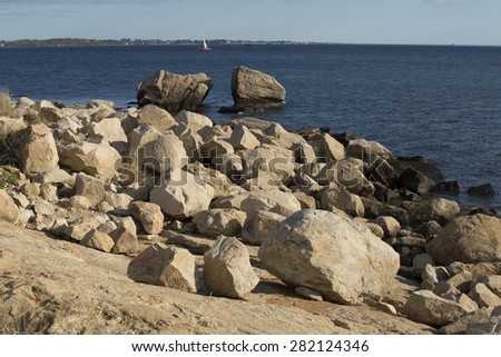 Boulders on the beach with a split rock and sailboat along the southern coastline of Connecticut in Bluff Point State Park, on Long Island Sound of the Atlantic Ocean. - stock photo