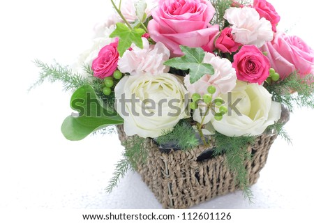 Bouquet from different pink seasonal flowers in basket isolated on white - stock photo