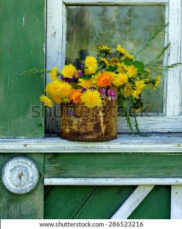 Bouquet In A Tin Is On The Old Window With Peeling Paint Wood