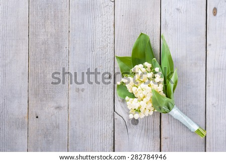 bouquet lily of the valley on natural wooden background