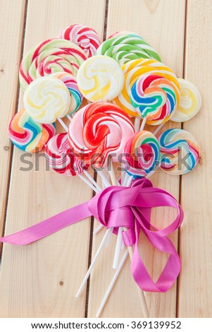 Bouquet made from colorful popsicles on wooden background - stock photo