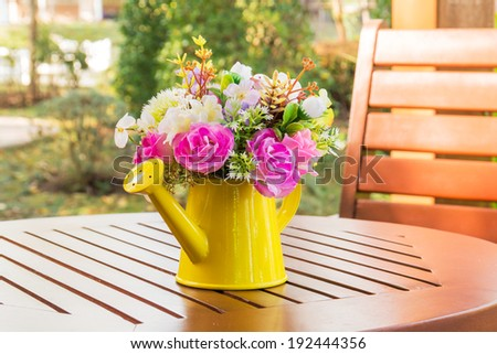 Bouquet of artificial flowers in watering can on wooden table