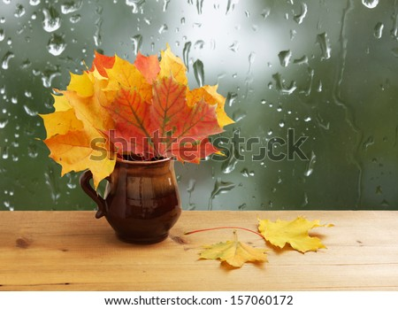 Bouquet of autumn leaves on  window sill - stock photo