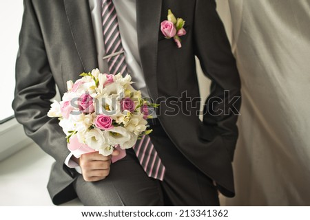 Bouquet of beautiful flowers in hands of the groom.