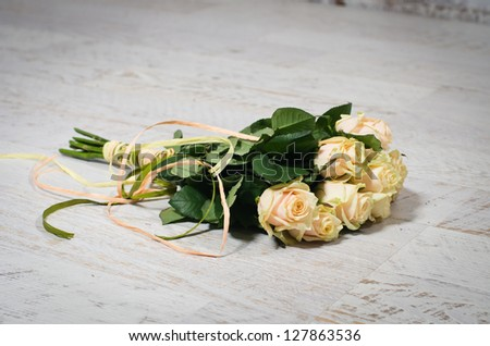 Bouquet of beautiful pastel roses lying on a white wooden floor - stock photo