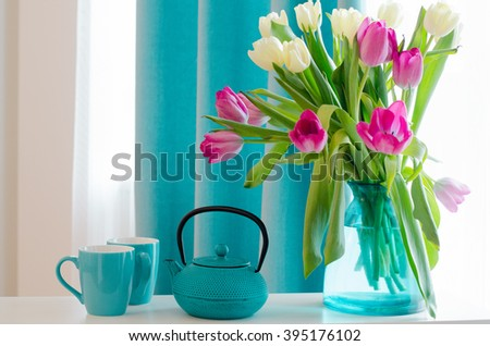 Bouquet of beautiful pink and yellow tulips in tiffany vase, cup, saucer and teapot. Free space for your text. - stock photo