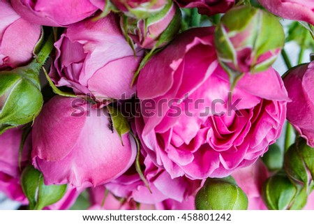 bouquet of beautiful pink peonies, roses with green leaves lie on a wooden table.