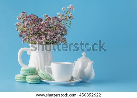 bouquet of blossoming oregano and tea with macaron - stock photo