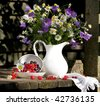 bouquet of bluebells and daisies in a white jug and berries - stock photo
