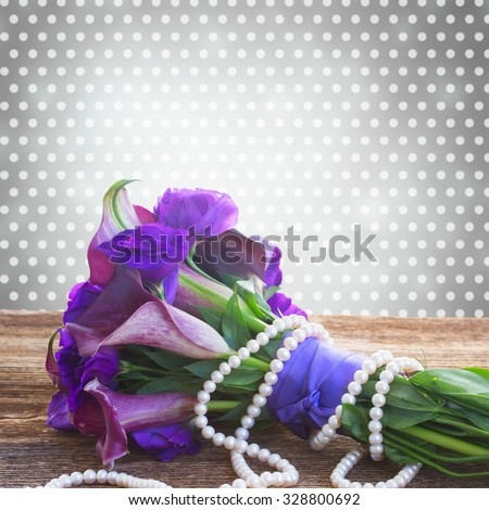 Bouquet of calla lilly and eustoma flowers  on wooden table - stock photo
