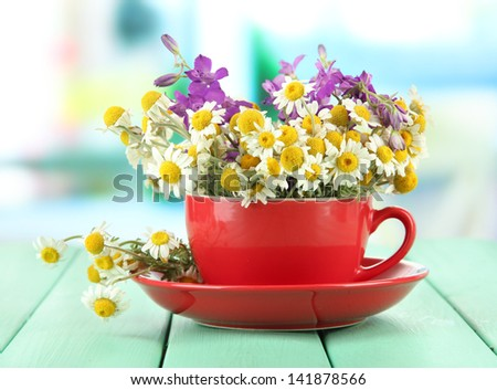 Bouquet of chamomile flowers in cup, on bright background - stock photo
