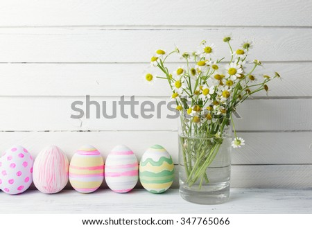 Bouquet of chamomiles in a glass vase and easter eggs in pastel color on white vintage planks - stock photo