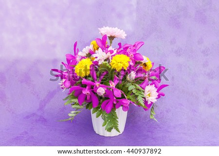 Bouquet of chrysanthemum and orchid flowers isolated on purple violet background.